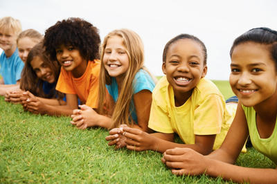 Smiling children laying on field